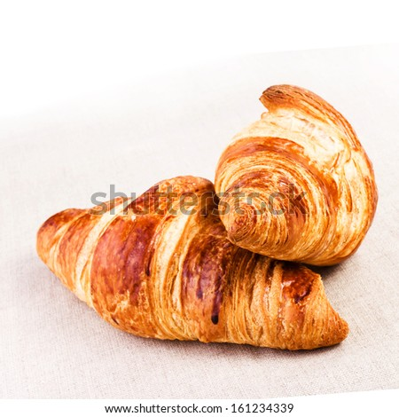 Two Fresh Croissants on linen tablecloth on a table, closeup. - stock photo