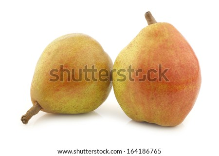 """two fresh """"doyenne de comice"""" pears on a white background - stock photo"""