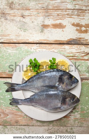 Two fresh fishes (Sparus aurata) with lemon and parsley on a plate served on rustic green table - stock photo