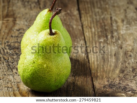 Two fresh green pear with drops of water on wooden table, selective focus - stock photo