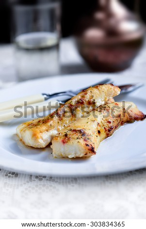 Two fresh grilled cod fillets with ginger, chilli and lime dressing against a rustic background with selective focus and copy space. The perfect image for your fish restaurant lunch menu. - stock photo
