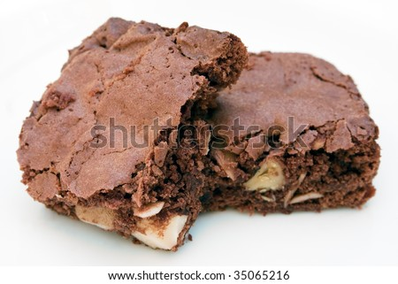 Two fresh home-made chocolate brownies stacked together on a white background
