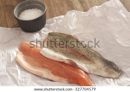Two fresh raw rainbow trout fillets displayed flesh side up and skin side up on a piece of crumpled white paper in a kitchen ready to prepare a tasty seafood meal - stock photo