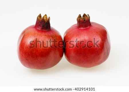 Two fresh red pomegranate fruits, on white background.