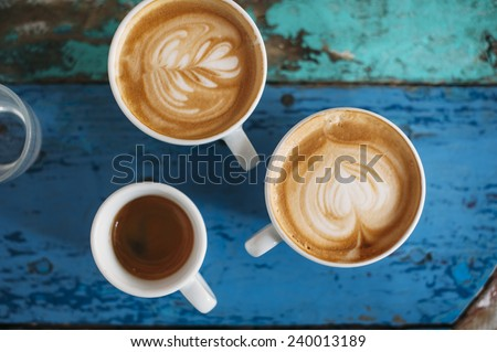 two fresh tasty cappuccino coffee cups with latte art on it and one espresso cup on the coffee table - stock photo