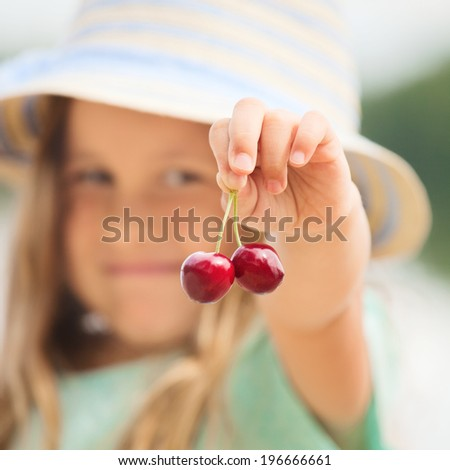 Two fresh tasty cherries in child's hand, outdoors - stock photo