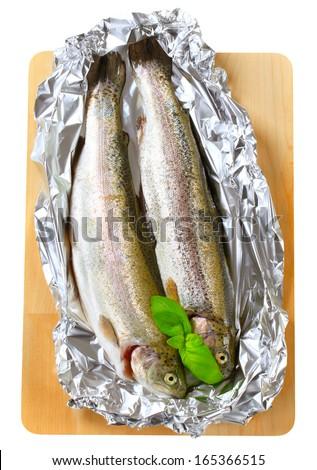 Two fresh trout on tin foil - cutout - stock photo