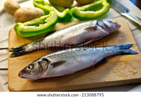 Two fresh whole uncooked cleaned sea bass on a wooden board with sliced green bell peppers being prepared for a delicious seafood dinner - stock photo