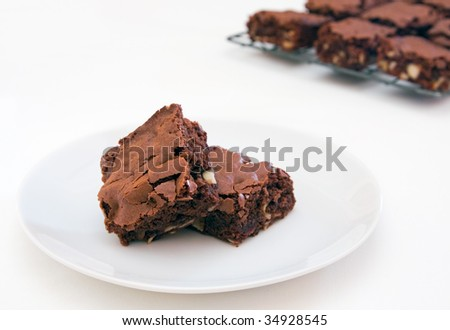 Two freshly baked brownie pieces on a white plate and tablecloth with a rack of extra brownies in the background - stock photo