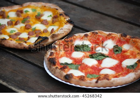Two freshly-made brick oven pizzas with fresh basil, mozzarella and sausage