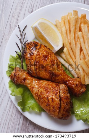 Two fried chicken drumsticks with french fries, rosemary, lemon and lettuce on a white plate. top view. close-up