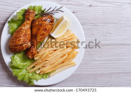 Two fried chicken drumsticks with french fries, rosemary, lemon and lettuce on a white plate. top view  - stock photo
