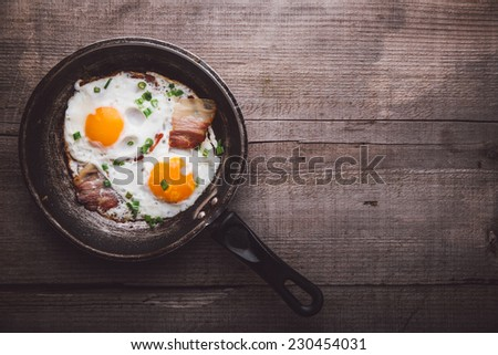 Two fried eggs with bacon and onion on a wooden table - stock photo