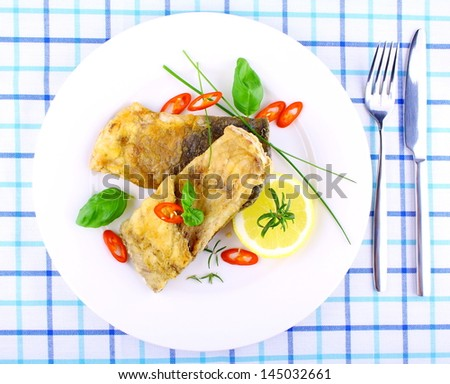 Two fried fish fillets with lemon slice on white plate, top view - stock photo