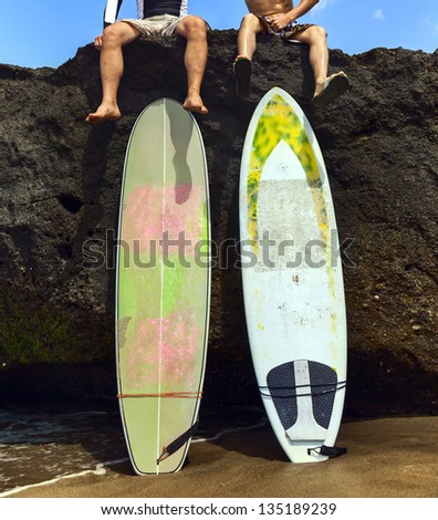 Two friend surfer sitting on rock with his legs dangling - stock photo