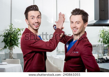Two friendly brothers twins in red jackets and blue sweater together having fun in the dinner room or the restaurant. Family relationships or friends in business - stock photo