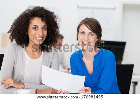 Two friendly businesswoman at the office sitting together at a desk discussing handheld paperwork and smiling at the camera