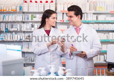 Two friendly  pharmacists in white uniform at the work in modern pharmacy