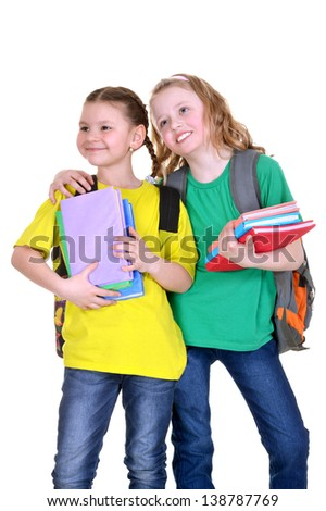 two friendly schoolgirl with textbooks in colorful t-shirts on white background - stock photo