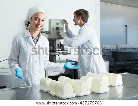 Two friendly smiling young technologists in lab coats working at dairy farm lab