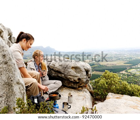two friendly women cook up some food while camping in the wilderness. outdoor hiking lifestyle concept - stock photo