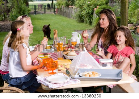 Two friends and their daughters having a summer picnic outdoors - stock photo