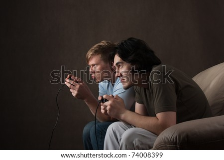 two friends are focused on playing video games on gray background - stock photo