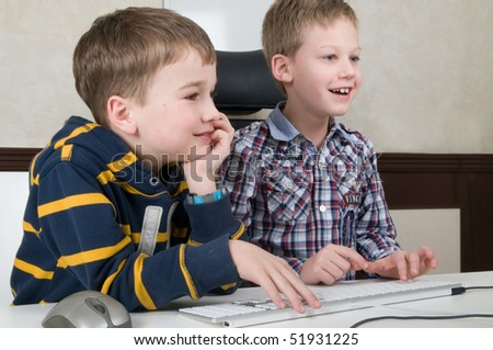 Two friends are having fun while working on a computer. - stock photo