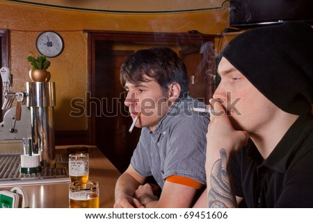 Two friends are sitting in a pub and smoke - stock photo