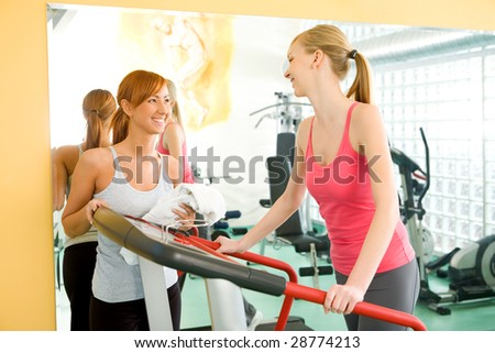 Two friends at gym. One of them walking on treadmill. They're talking and smiling.