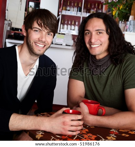 Two friends at the coffee shop with red mugs - stock photo