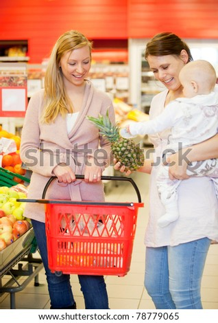 Two friends buying groceries, one with a child - stock photo