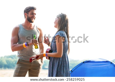 Two friends chatting in campsite on a sunny day - stock photo