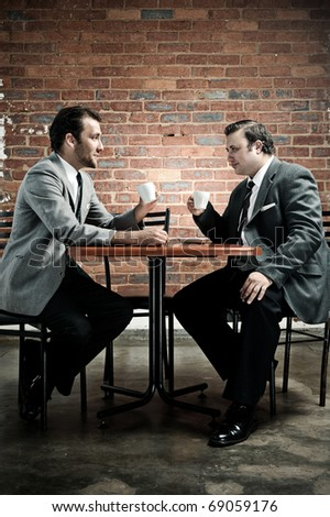 Two friends discuss the taste of coffee while wearing suits - stock photo
