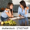 Two friends discussing recipes over a cookbook - stock photo