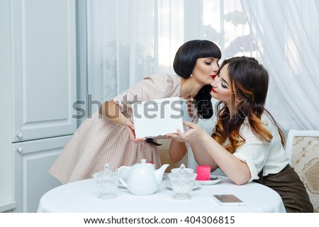 Two friends drink tea with cake. Tea party. Home gatherings. The girl gives to the girlfriend a birthday gift and kisses her on the cheek. - stock photo