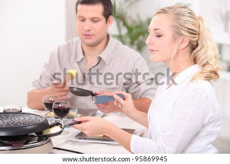 Two friends eating raclette - stock photo