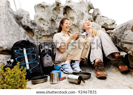 two friends enjoy a laugh together while camping outdoors after a hike in the wilderness - stock photo