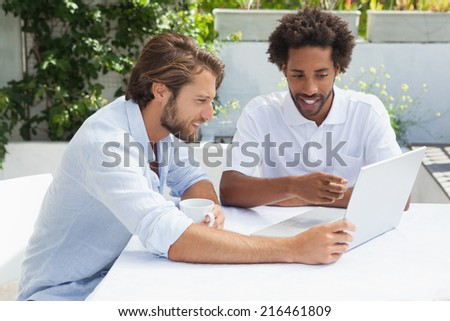 Two friends enjoying coffee together with laptop outside at the coffee shop
