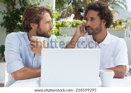 Two friends enjoying coffee together with laptop outside at the coffee shop - stock photo