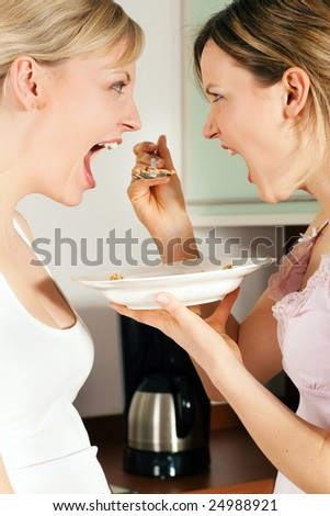 Two friends (female) having a lot of fun eating cereals for breakfast - stock photo