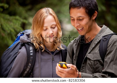 Two friends geocaching in the forest wth a gps