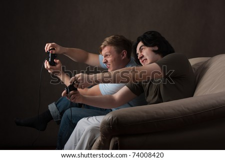 two friends go crazy while playing video games on gray background - stock photo