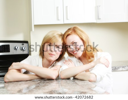 Two friends having a chat in the kitchen, redhead and blonde