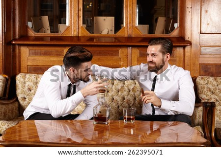 Two friends having a glass of whiskey and a nice conversation - stock photo
