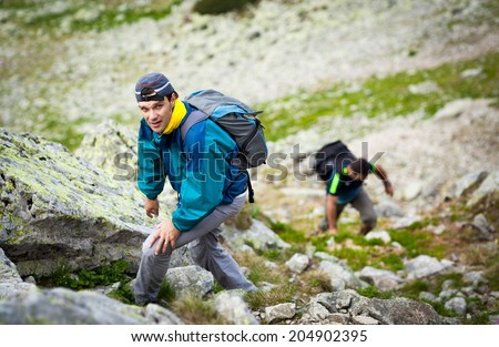 Two friends hiking together in mountains, with backpacks