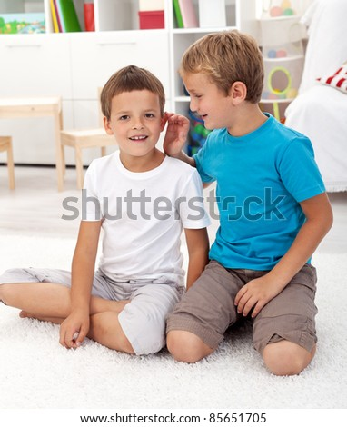 Two friends in the kids room talking secrets and having fun - stock photo