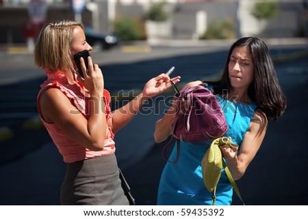 Two friends juggle multiple tasks on city street. - stock photo