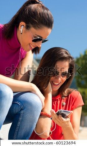 two friends listening to music in the park - stock photo
