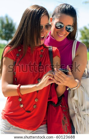 two friends looking at cell phone - stock photo